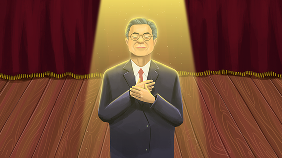 An illustration of South Korean President Moon Jae-in standing on a theatre stage with his hands in front of his chest, looking upwards.