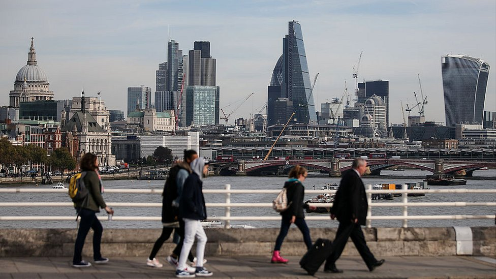 Pedestrians waling through Waterloo Bridge with the skyline of the City of London in the background