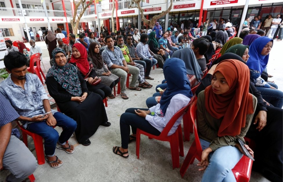 People sit in line as they wait to cast their votes at a polling station during the presidential election in Male, Maldives