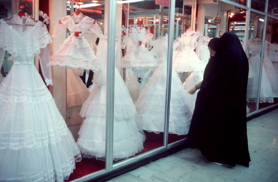 Two women wearing black chadors look at wedding dresses through glass windows in 1986
