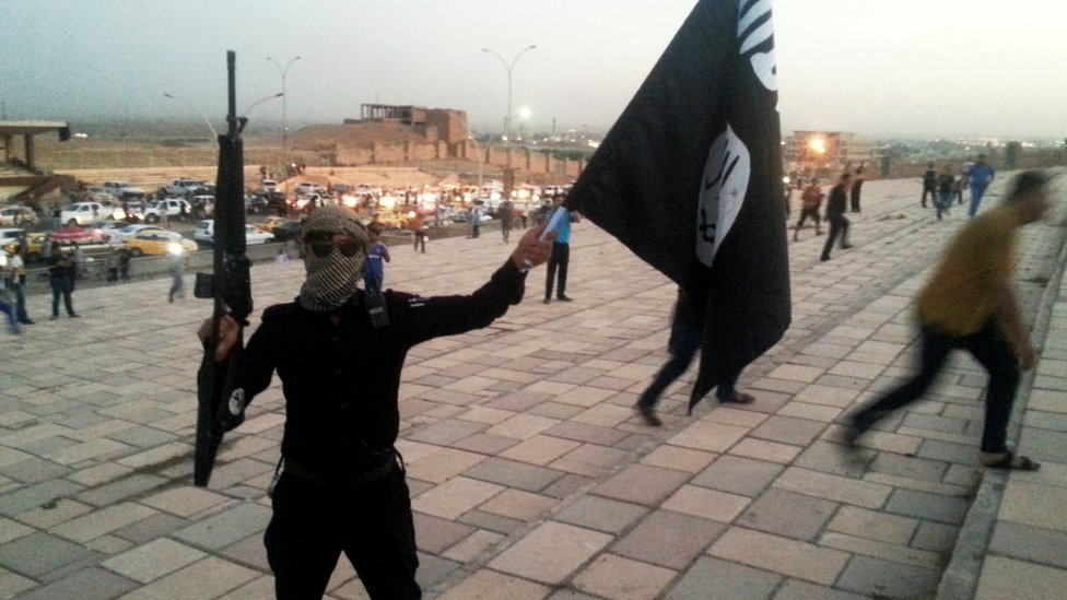 An Islamic State of Iraq and the Levant (ISIL) militant holds up a black banner and a rifle on a street in the city of Mosul on 23 June 2014