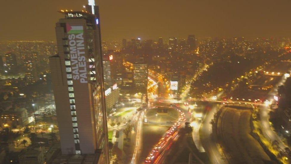"""El edificio Torre Telefónica, ubicado en Plaza Italia, en el centro de Santiago, fue iluminado con la frase """"Salvemos Palestina"""" el martes 18 de mayo."""