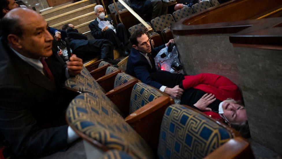El representante Jason Crow (centro), quien sirvió previamente en el Ejército de Estados Unidos, reconforta a la representante Susan Wild, mientras los seguidores de Trump irrumpían en la sede del Congreso.