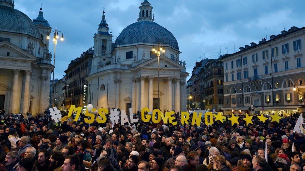 """Velika gužva na gradskom trgu. Iznad njih su naređana slova i ispisano: """"Pokret 5 Zvezda u vladu"""""""