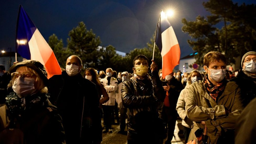 People attend a memorial march in Conflans-Sainte-Honorine, northwest of Paris