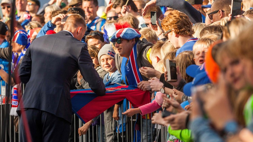 A Iceland national football player signs an autograph as he arrives with his team in Reykjavik on July 4, 2016 while people in the streets greet them as winners after they lost against France during the the Euro 2016