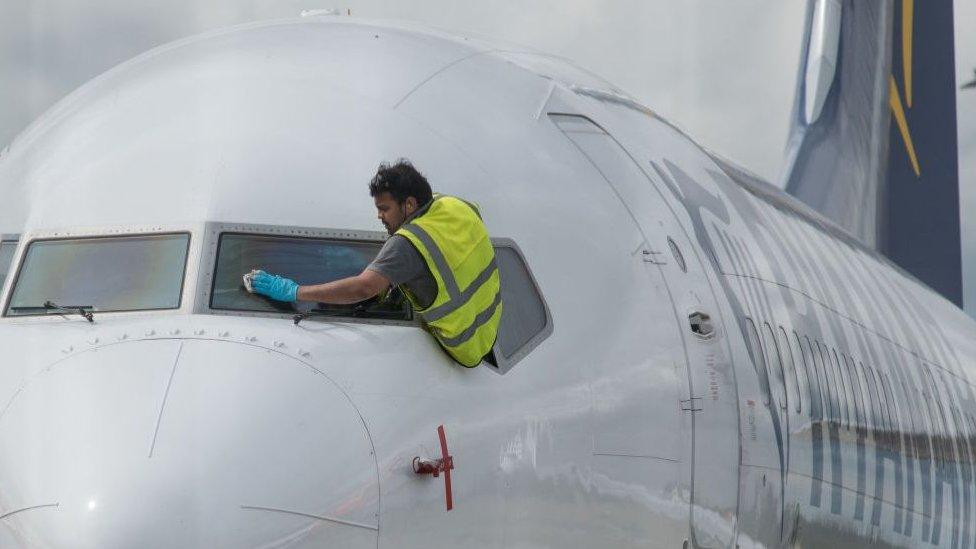 Un trabajador limpiando las ventanas de un avión