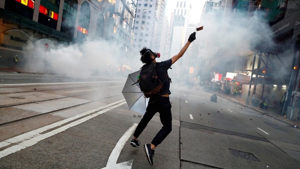"""An anti-government protester reacts as police fire tear gas during a march billed as a global """"emergency call"""" for autonomy, in Hong Kong, China, on 2 November 2019"""