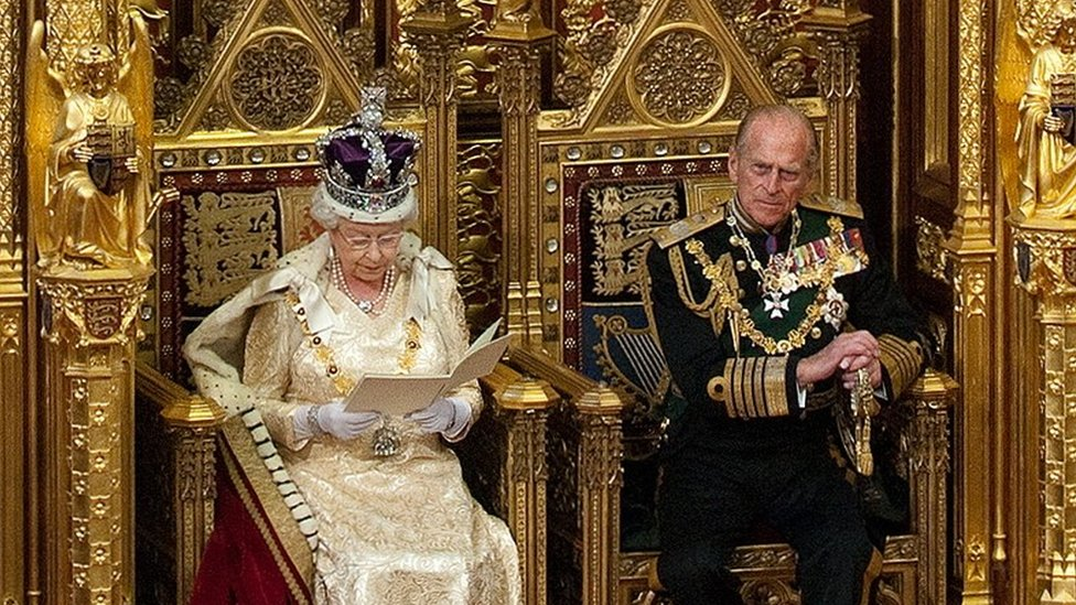 La reina Isabel II de Inglaterra leyendo un discurso desde un trono de oro