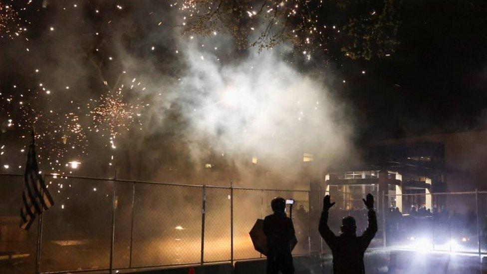 Foto de fuegos artificiales siendo lanzados hacia la comisaría de policía en Brooklyn Center, Mineápolis.