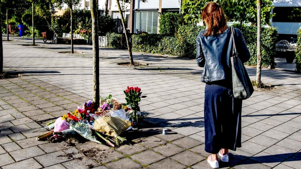 A woman walks by flowers laid outside the home of the murdered lawyer Derk Wiersum, on September 19, 2019