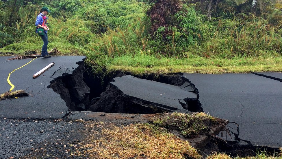 A geologist inspects cracks on a road in Leilani Estates, following eruption of Kilauea volcano, Hawaii on 17 May 2018.