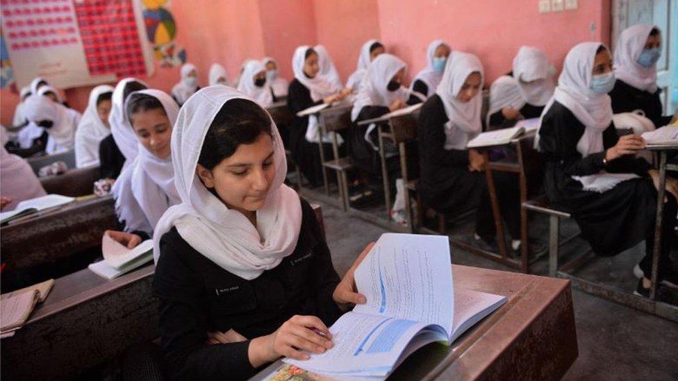 Girls sitting at desks reading