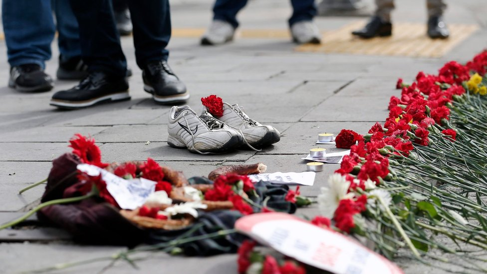 People place flowers and shoes on the ground after a twin bombing in Ankara, Turkey (12 October 2015)