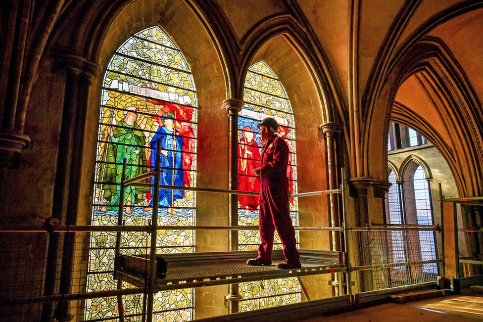 Head glass conservator Sam Kelly inspects the Angeli Laudantes and Angeli Ministrantes stained glass windows at Salisbury Cathedral as restoration gets under way.