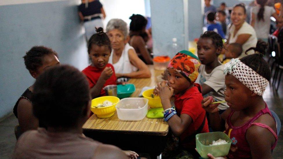 Niños almorzando en un comedor comunitario en Petare (Caracas).