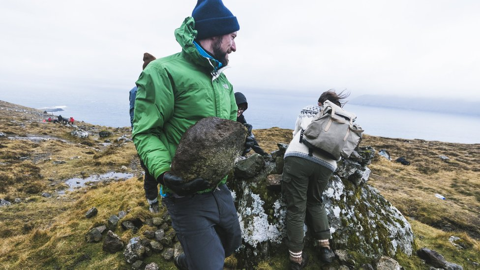 A Brown Team voluntourist carries a big boulder to be placed on a cairn