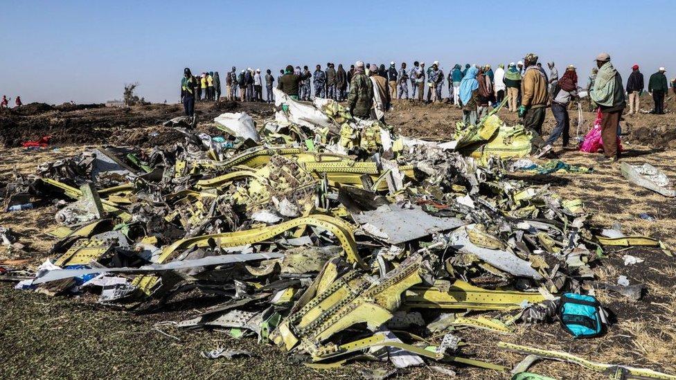 Personas frente a los restos del avión Boeing 737 MX de Ethiopia Airlines.