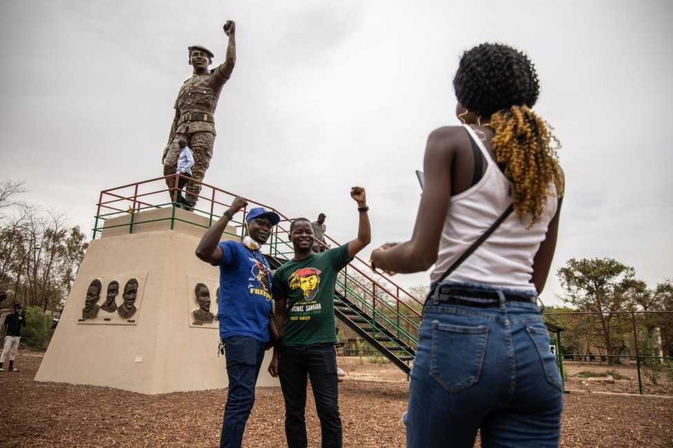 People pose for photos with the second bronze statue of Burkina Faso's former President Thomas Sankara on 17 May 2020.
