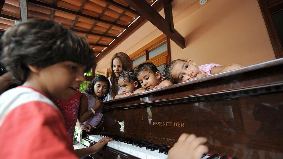 Flordelis con varios de sus hijos tocando el piano.