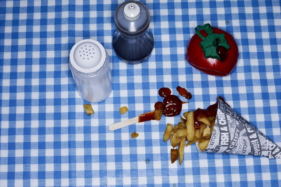 Mesa con sal, salsa de tomate, vinagre y papas fritas
