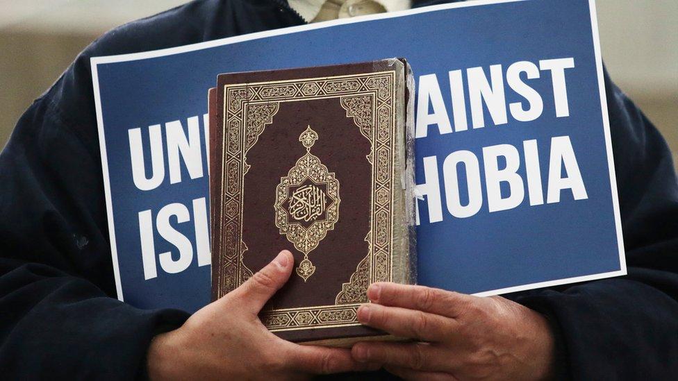 شخص يحمل القرآن ولافتة ضد الإسلاموفوبيا