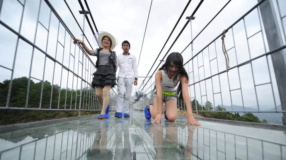 Tourists walk on a suspension bridge made of glass at the Shiniuzhai National Geological Park in Pingjiang County
