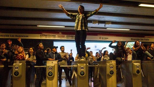 Manifestantes sobre los torniquetes del metro de Santiago de Chile