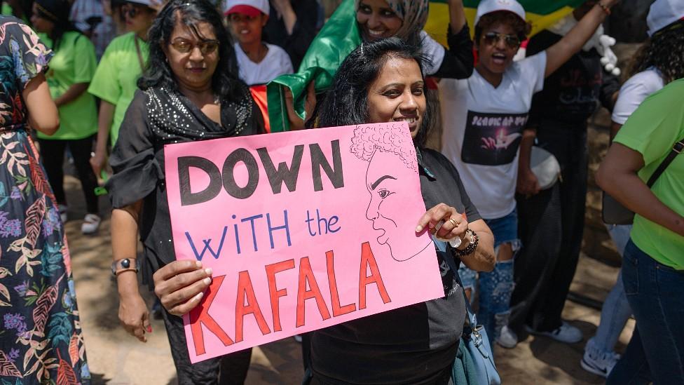 """Mujeres protestando en Líbano con un cartel que dice """"abajo el kafala"""". 2019"""