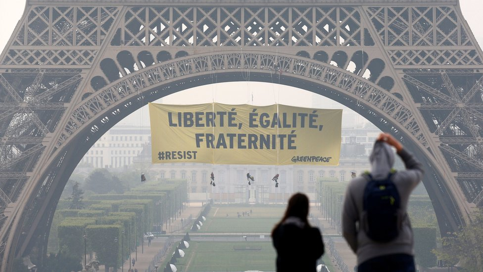 "Tourists walk at Trocadero square as activists from the environmentalist group Greenpeace unfurl a giant banner on the Eiffel Tower which reads ""Liberty, Equality, Fraternity"" in Paris, France (May 5, 2017)"