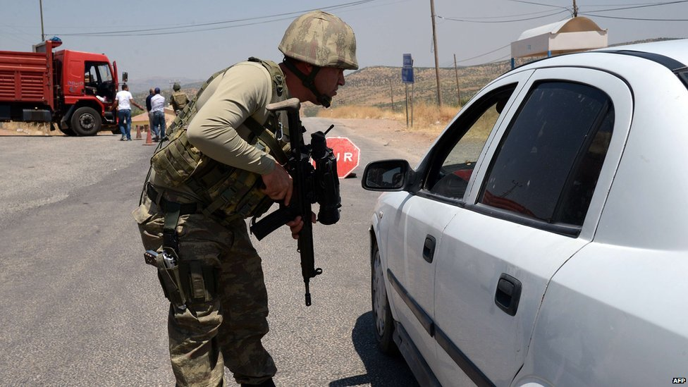 A Turkish solders check cars at a check point in Diyarbakir on July 26, 2015