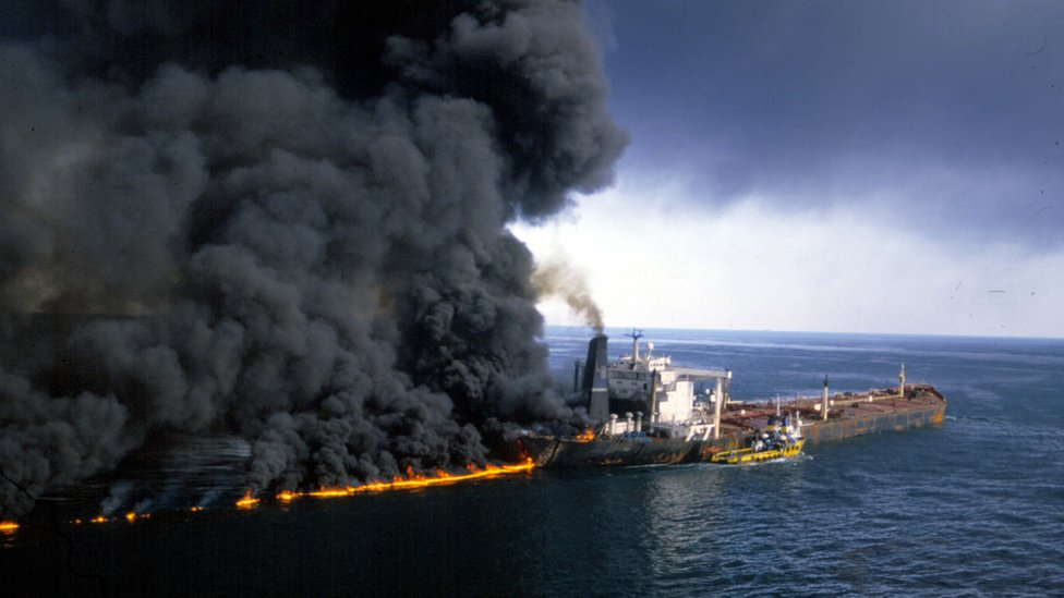 On an open sea, a large industrial ship is seen burning, with thick clouds of black smoke billowing out of it