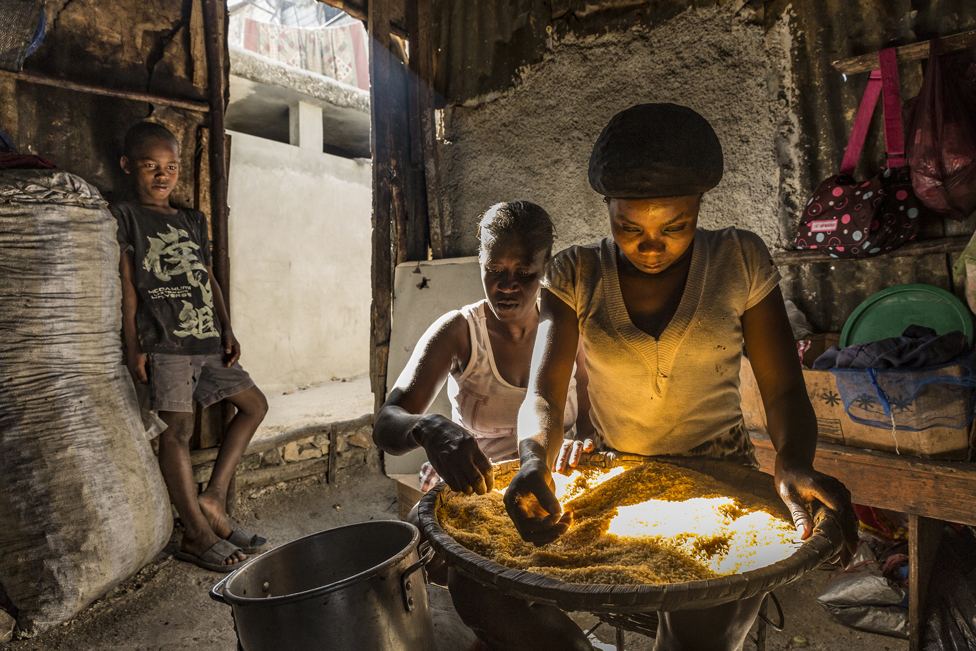 Two women clean rice at one of the slum's restaurants