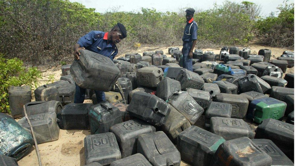 Policías con bidones de combustible confiscado.