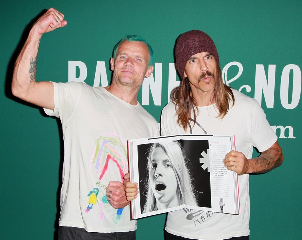 Flea and Anthony Kiedis hold a biography of the Red Hot Chili Peppers