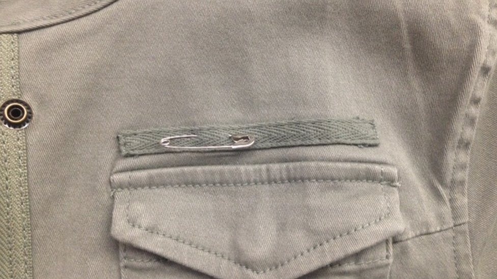 A picture of a safety pin on a jacket lapel.