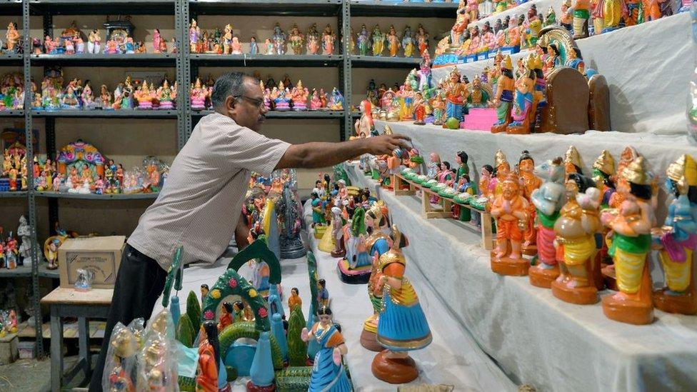 Un hombre rodeado de muñecas de juguete.