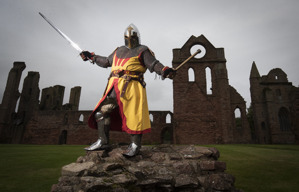 A historical actor wearing a suit of armour at Arbroath Abbey