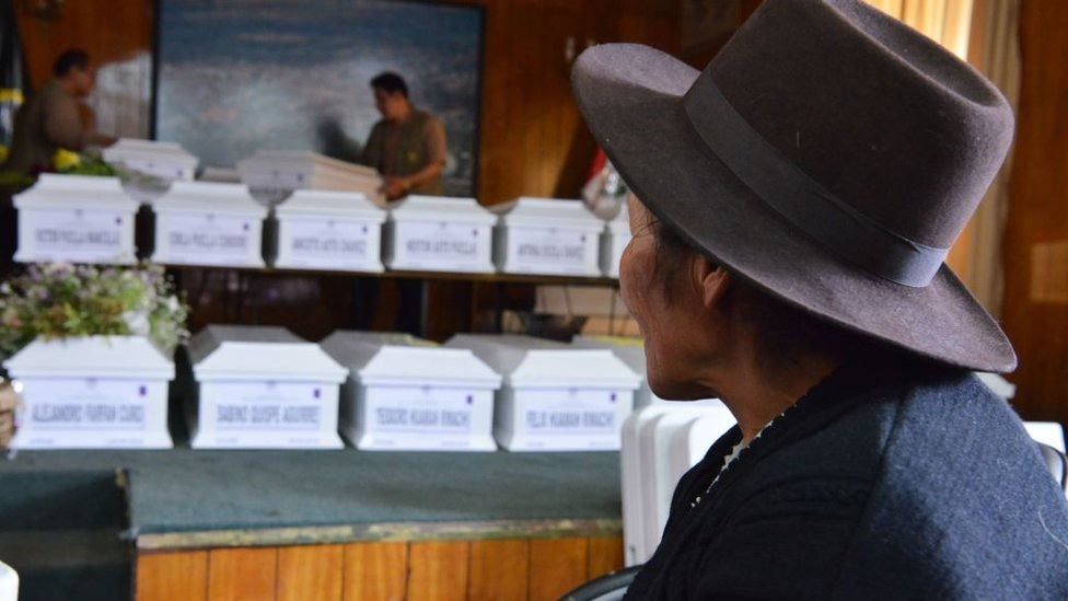 Una mujer frente a unos ataúdes de personas muertas durante el conflicto interno en Perú.