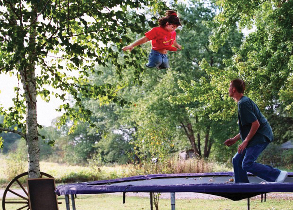 Jennifer bounces on the trampoline with her brother