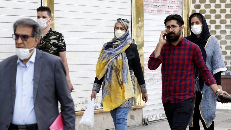 مواطنون يسيرون بالأقنعة غي شوارع طهران