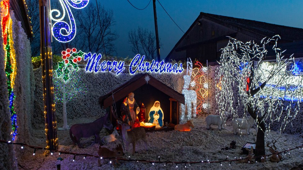 An illuminated nativity scene, Merry Christmas sign and light-covered trees.