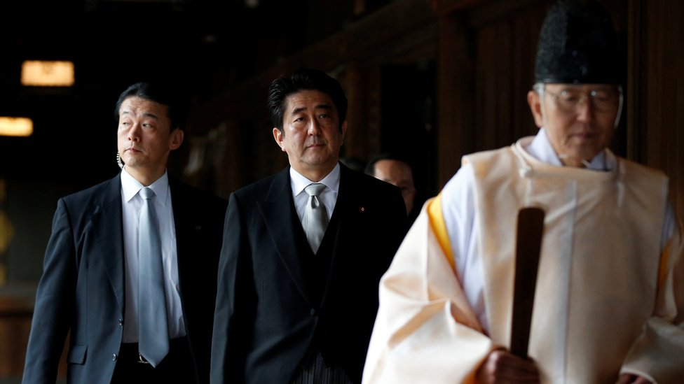 "Japan""s Prime Minister Shinzo Abe (C) is led by a Shinto priest as he visits Yasukuni shrine in Tokyo December 26, 2013"