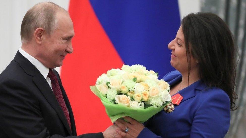 Russian President Vladimir Putin presents flowers to editor-in-chief of Russian broadcaster RT Margarita Simonyan in May