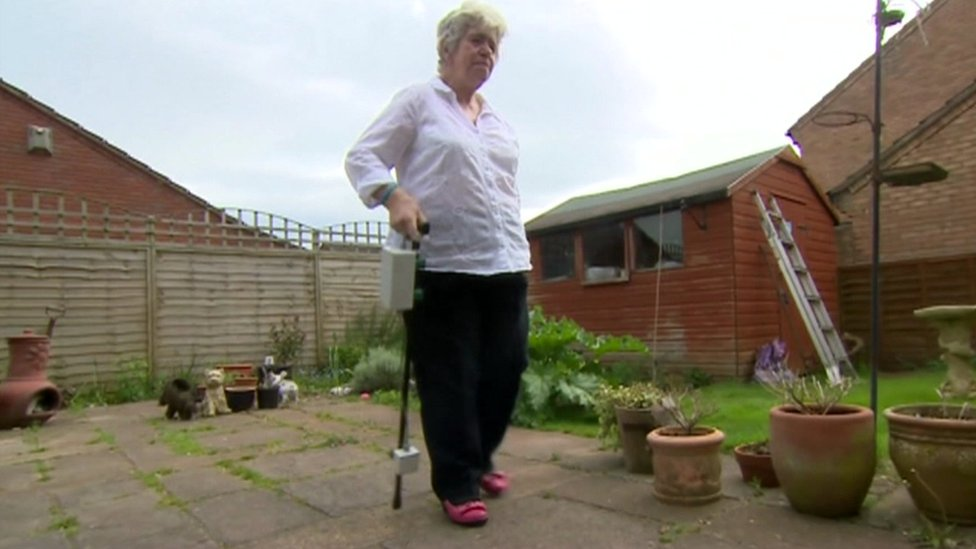 Woman uses special stick in a garden