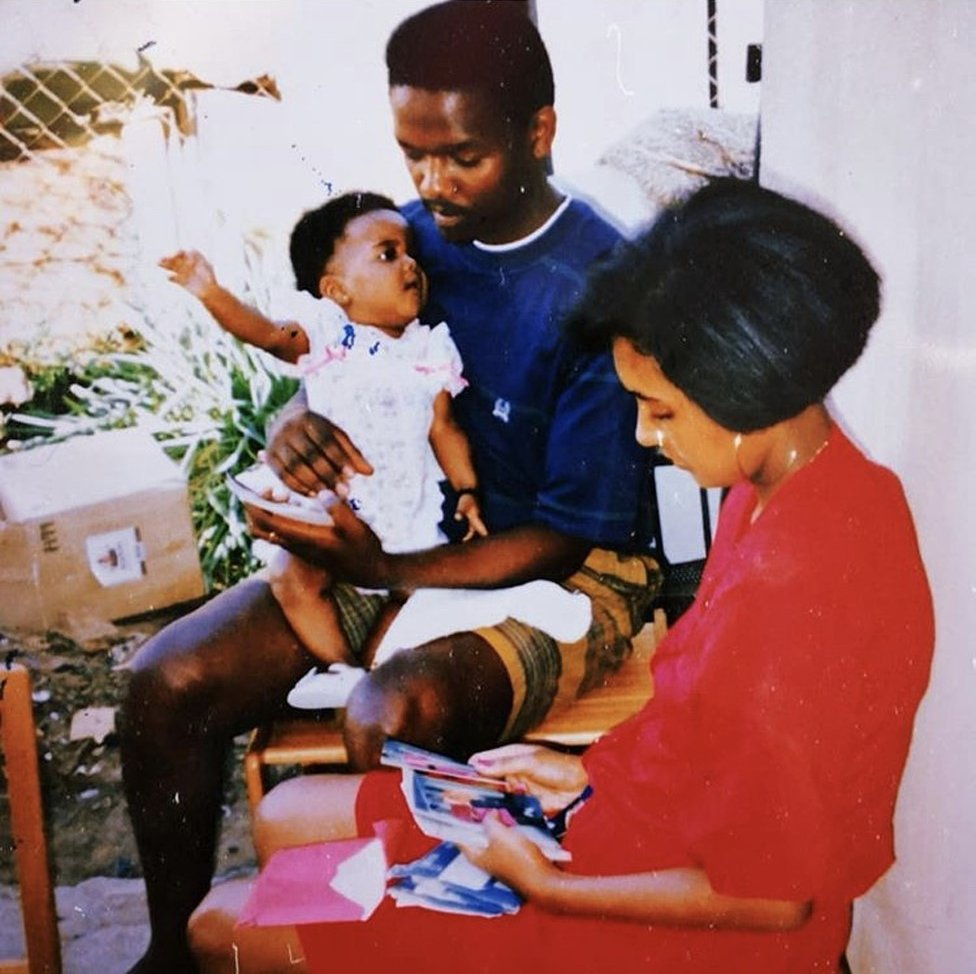 A picture of Candice Mama as a baby with her mother and father