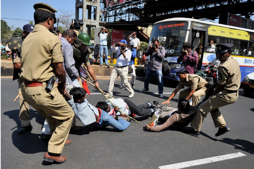 Police try to detain students protesting against the California-based Tri-Valley University outside the US consulate in Hyderabad city in 2011.