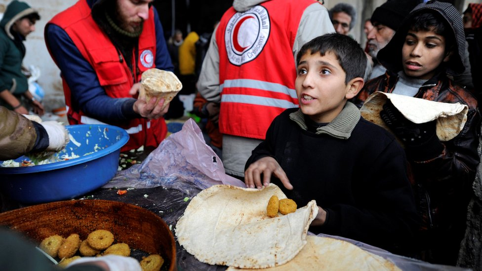 Displaced people from eastern Aleppo get food aid from the Syrian Red Crescent at a shelter in government-controlled Jibreen, Syria (30 November 2016)
