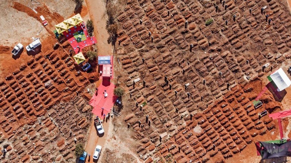 This aerial picture shows several funerals being celebrated at the Olifantsvlei Cemetery in Soweto, on July 25, 2020
