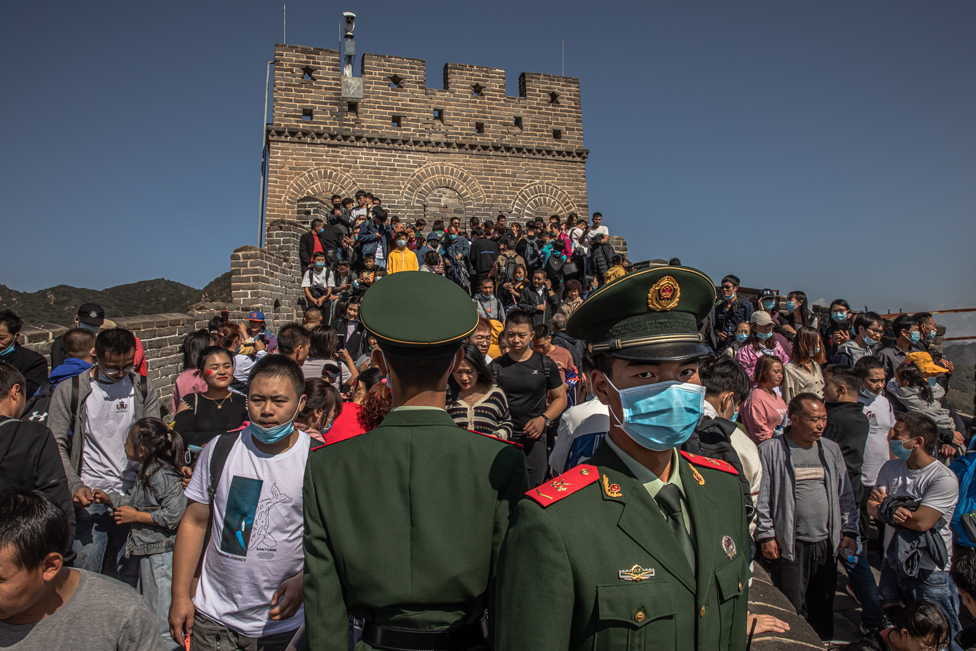 Chinese soldiers stand guard as tourists visit the Badaling section of the Great Wall